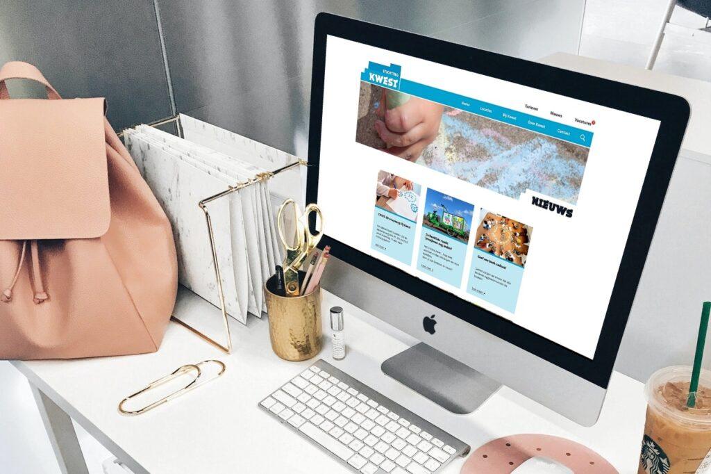 Mac met schermafbeelding van website Stichting Kwest en diverse accessoires op bureau.