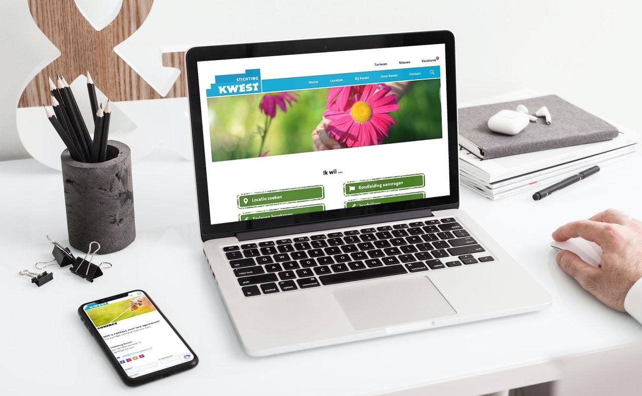 Laptop en diverse accessoires op tafel. Schermafbeelding van website Stichting Kwest op scherm laptop.