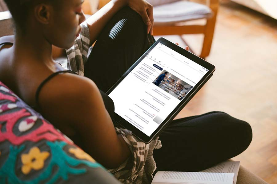 Dame op bank met tablet maakt gebruik van voorzieningen webtoegankelijkheid